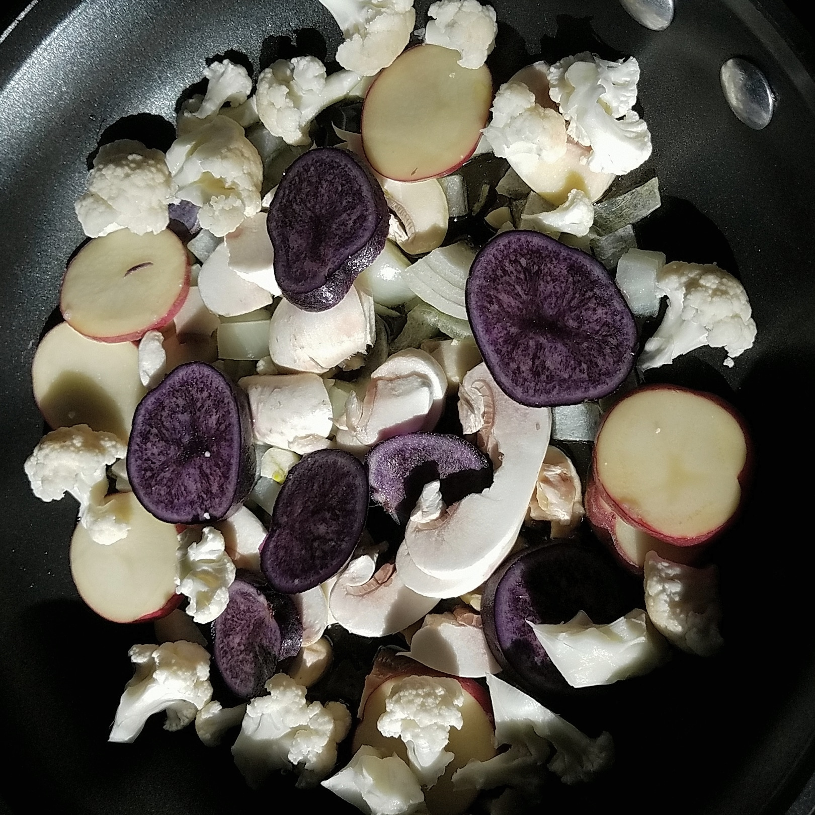 Purple potatoes, mushrooms, cauliflower and other veggies in a skillet getting ready to be cooked.