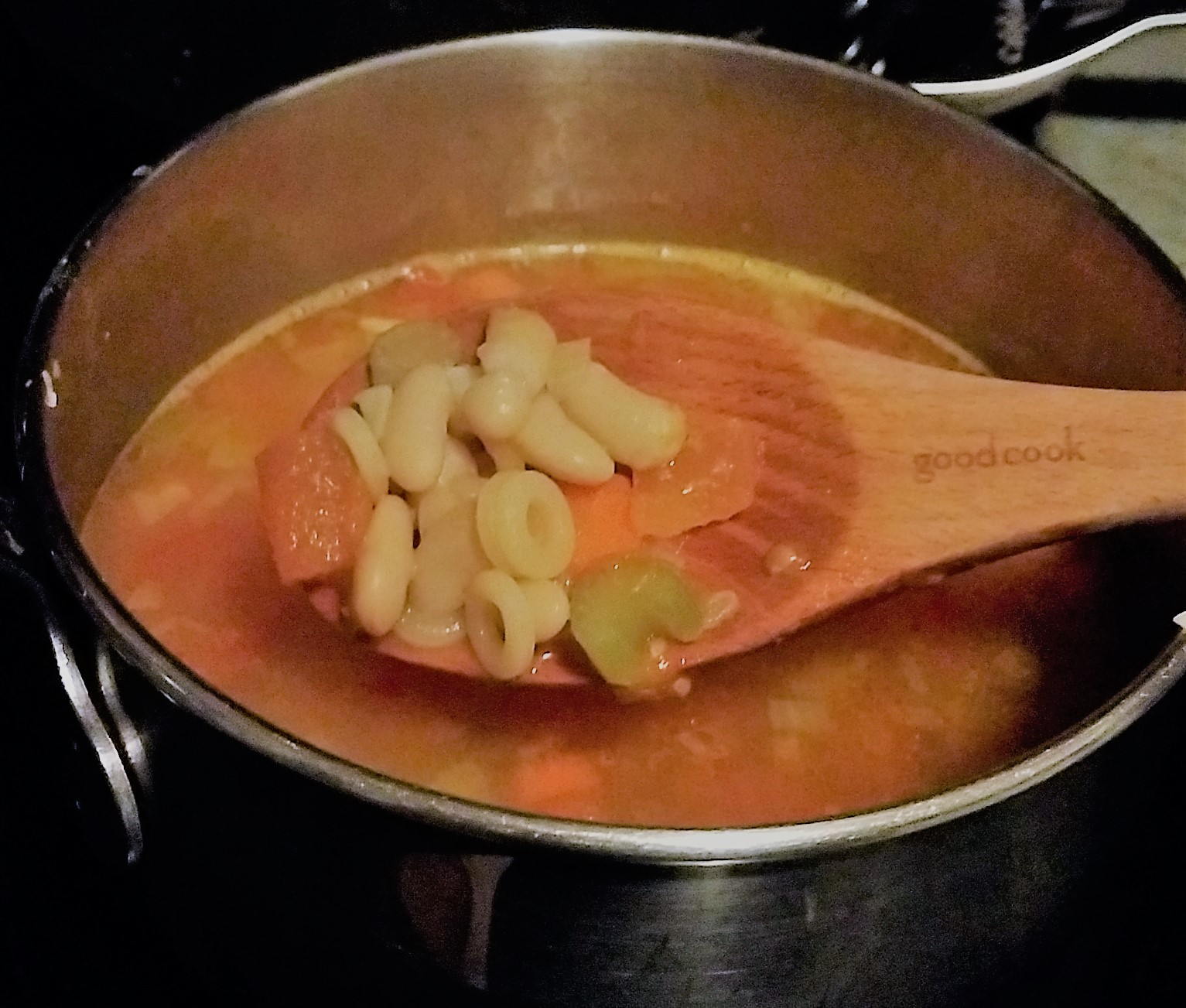 A pot of soup with some tomato, white beans, celery and pasta rings on a wooden spoon.